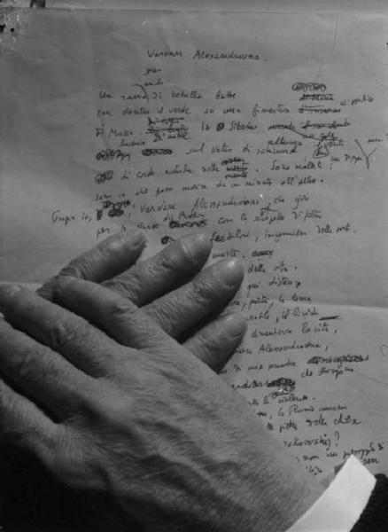 Manoscritto di una poesia e le mani del poeta.